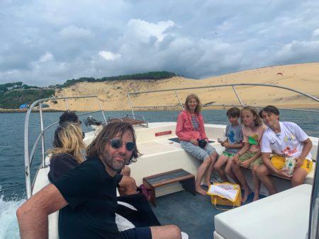 Une famille de touristes apprécie une balade en bateau le long de la dune du Pilat