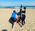 3 yoginis en pleine séance de yoga sur le sable