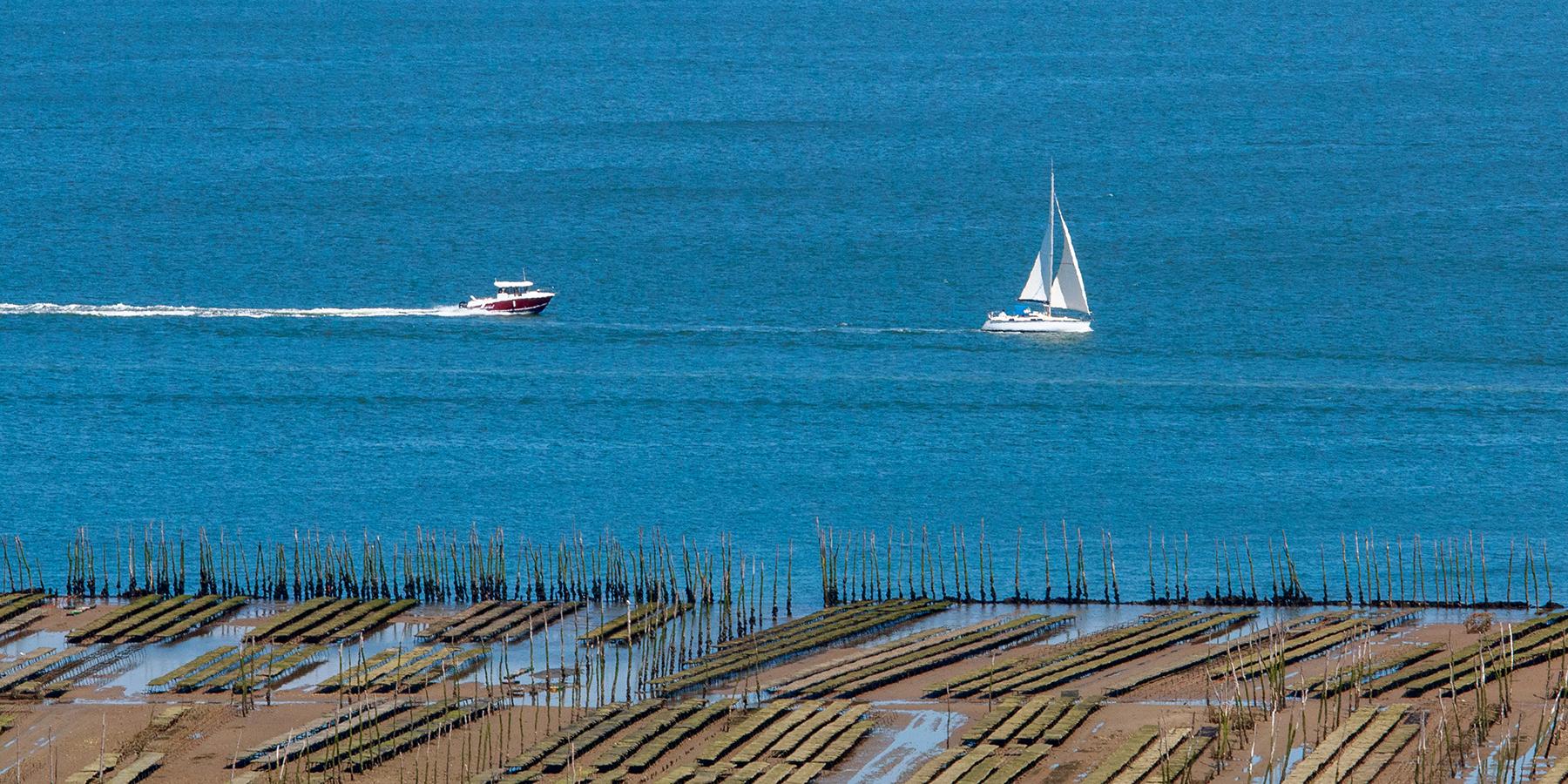 Bateau à moteur et voilier sur le bassin d'Arcachon